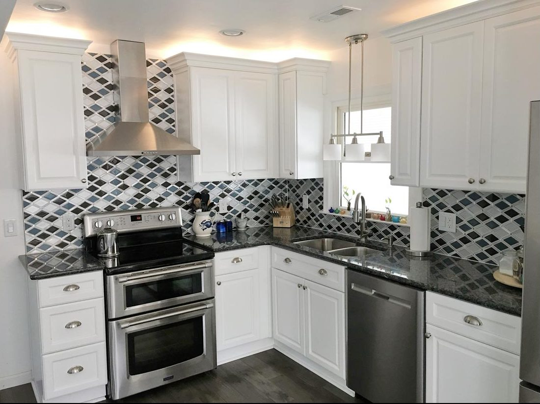 kitchen remodeling featuring stove ventilation system and decorative wall splash
